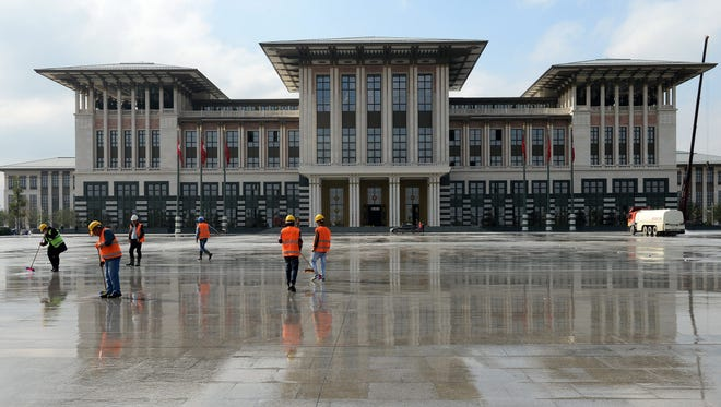 Workers clean the area in front of the new Turkish Presidential Palace in Ankara, Turkey, on Oct. 28.