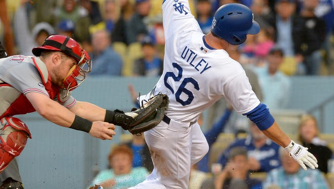 Los Angeles Dodgers second baseman Chase Utley (26) beats the tag by Cincinnati Reds catcher Tucker Barnhart (16) as he scores a run in the first inning on a single by shortstop Corey Seager (5) at Dodger Stadium.