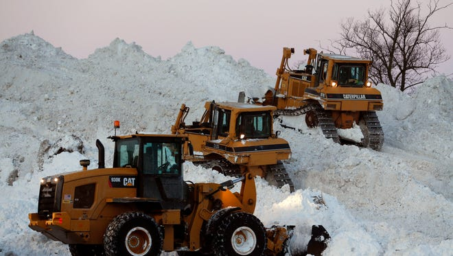 Heavy equipment moves snow that was removed from south Buffalo neighborhoods after heavy lake-effect snowstorms on Friday, Nov. 21, 2014, in Buffalo, N.Y.  A snowfall that brought huge drifts and closed roads in the Buffalo area finally ended Friday, but rain and flooding continue to trouble the area.