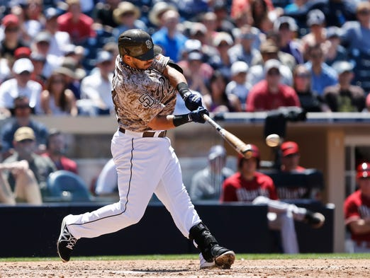 San Diego Padres' Rene Rivera drives a double down the left field line to drive in two runs against the Arizona Diamondbacks during the fourth inning of a baseball game Sunday, May 4, 2014, in San Diego.