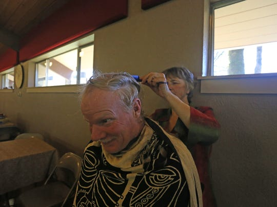 Jack Cook, 50, gets a haircut from a volunteer at Aldersgate Camps and Retreats in Turner, Ore., on Dec. 25, 2016. Volunteers served 120 area homeless during the annual Room at the Inn event.