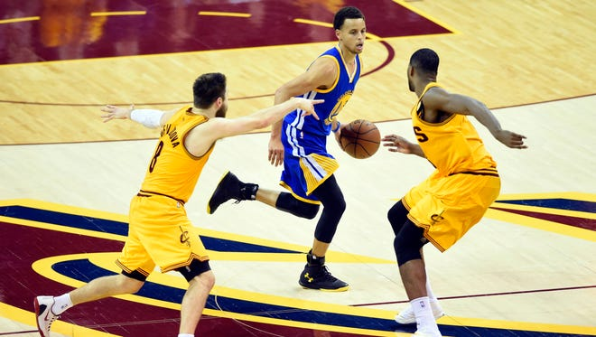 Golden State Warriors guard Stephen Curry dribbles against Cleveland Cavaliers guard Matthew Dellavedova (8) and center Tristan Thompson (13) in Game 3 of the NBA Finals.