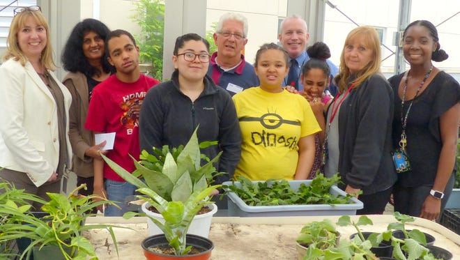 Center for Lifelong Learning students, Greenhouse Committee members and Principal Mary Beth Conley (left) in the greenhouse, behind the Christmas Cactus in the rectangular bin. The Christmas Cactus was a donation from ESCNJ Board Vice President Bill Petscavage (center).