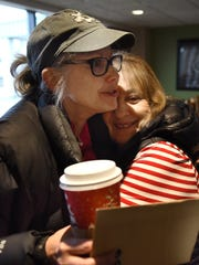 Northville Civic Concern director Marlene Kunz (right) shares a hug with friend Katherine Purcell at the Dec. 10 party.