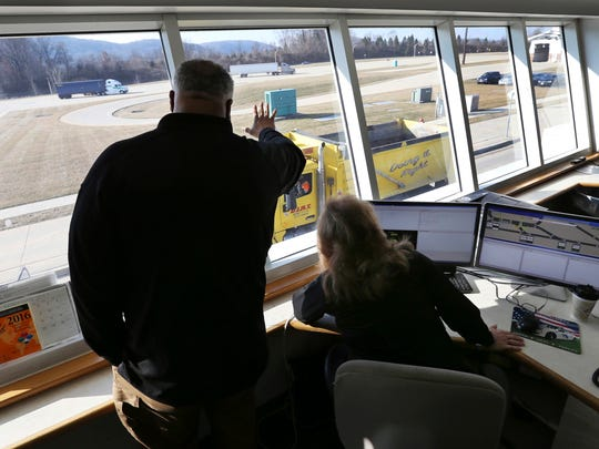 In this Monday, Feb. 6, 2017, photo, weigh master, Glenn Riley, signals a truck driver as fellow weigh master, Barbara Garland looks on, while they weigh and screen trucks passing through the Greenwich truck weigh station on Interstate 78, in Greenwich Township, N.J. One of the first lines of defense against New Jersey's opioid epidemic is the highway truck weigh station.