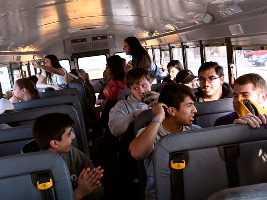 Abilene High band members talk while waiting for their bus to depart campus Friday.