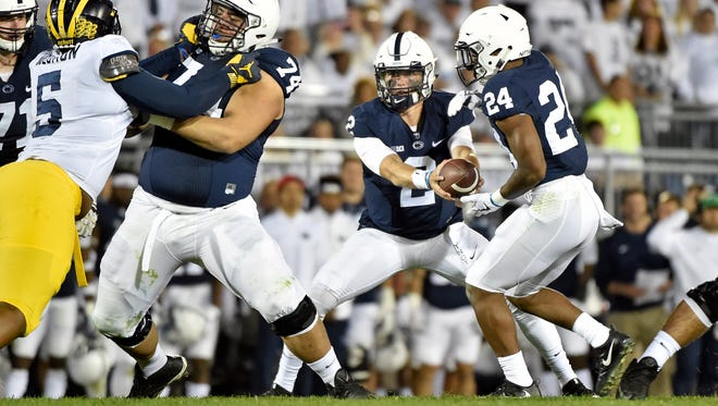 Penn State quarterback Tommy Stevens hands the ball to Miles Sanders in the second half of an NCAA Division I college football game Saturday, Oct. 21, 2017, at Beaver Stadium. The No. 2 Penn State Nittany Lions defeated Michigan 42-13, improving their season record to 7-0.