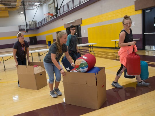From left, San Juan College High School student senate members Hannah Duckett, Heather Wheeler, Andrew Polanco and Mandi Tamporello help set up a booth for the Salvation Army Thursday at the Health and Human Performance Center At San Juan College.