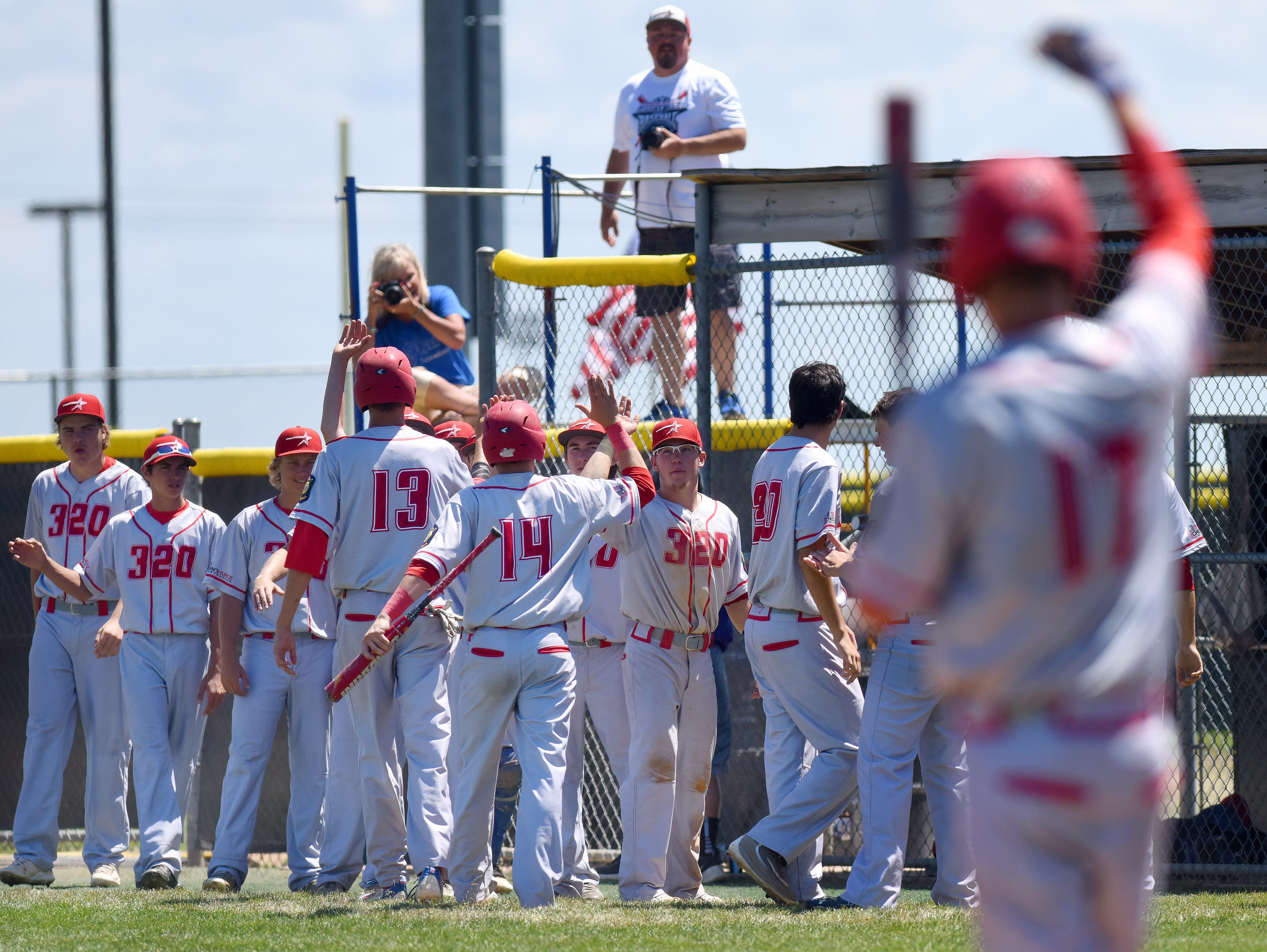 Rapid City Post 320 celebrate with teammates after scoring against Sioux Falls East Post 15 during the American Legion Class A Baseball State Tournament at Harmodon Park on Saturday afternoon.