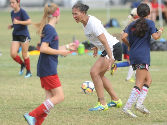 Shannon Boxx works with youngsters during a drill at