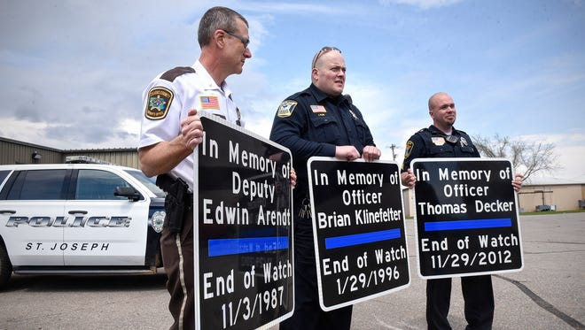 Stearns County Chief Deputy Bruce Bechtold, left, St. Joseph Police Chief Joel Klein, center, and Cold Spring-Richmond Police Chief Jason Blum hold signs dedicated to local officers killed in the line of duty Wednesday, May 3, at the Stearns County public works facility.