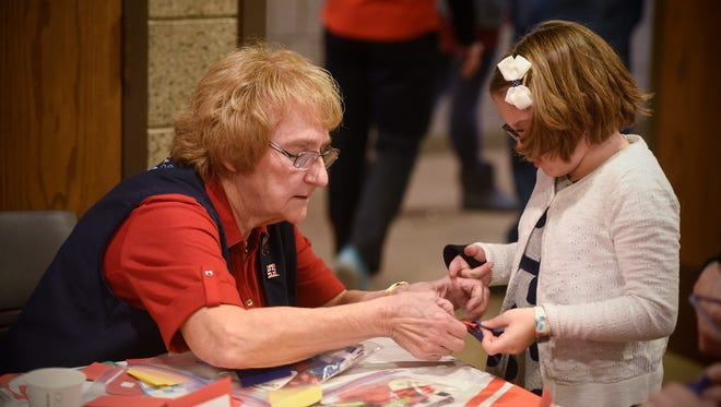Monica Oseid helps children make traditional Norwegian crafts during KringleFest Saturday, Dec. 2, at the Stearns History Museum in St. Cloud.