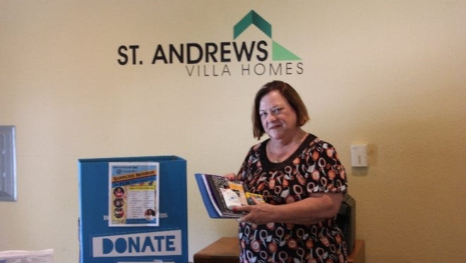 Cathy Prisco, sales manager at the Villas of St. Andrews, adds a donation to the Boys and Girls Club school supplies collection box.