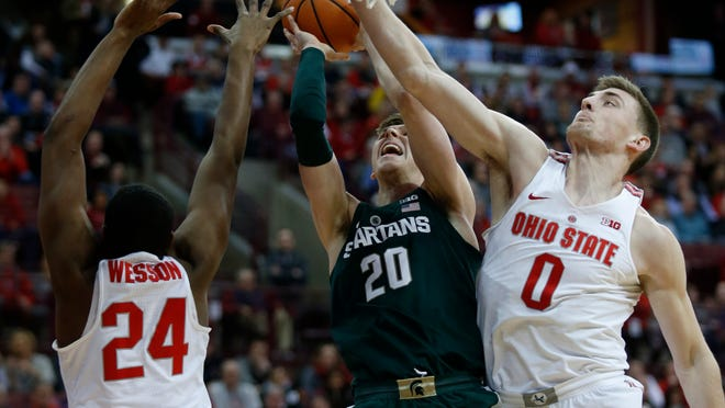 MSU guard Matt McQuaid goes up to shoot between OSU forward Andre Wesson, left, and center Micah Potter during the first half in Columbus, Ohio on Sunday.