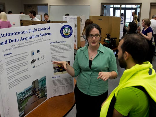 FGCU senior Lindsey Carboneau talks with Antuan Vazquez about one of her three projects during the STEM Undergraduate Research and Internship Symposium at FGCU on Friday.