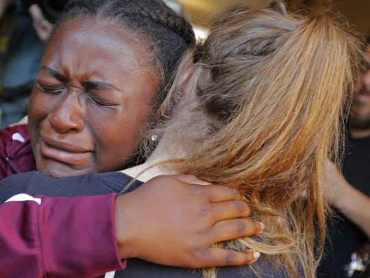 Marla Eveillard, 14, cries as she hugs friends before the start of a vigil at the Parkland Baptist Church, for the victims of the shooting at the Marjory Stoneman Douglas High School in Parkland, Fla., Thursday, Feb. 15, 2018. (AP Photo/Gerald Herbert)