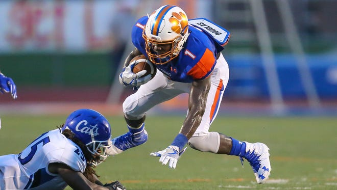 Madison Central's Tyshaun White (1) is tripped by Meridian's C. J. Mcclelland (25) in the second quarter of Friday's game.