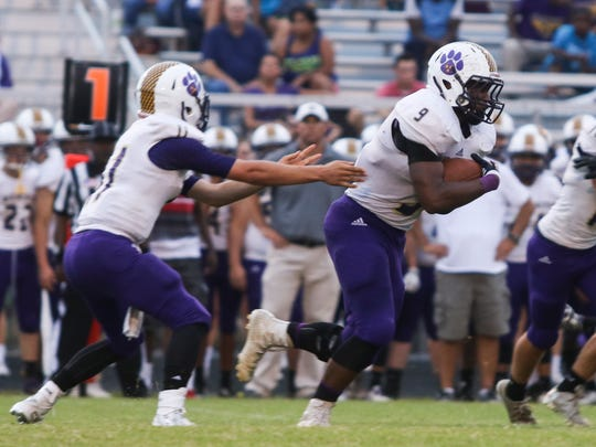 Clarksville High's Skyler Luna (11) hands the ball off to Brevon Johnson (9) during their game at Kenwood High last Friday. Clarksville won the game 28-24.