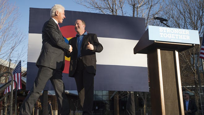 U.S. Representative Jared Polis (right) welcomes former President Bill Clinton to the stage as Clinton campaigns for his wife, democratic candidate Hillary Clinton, during a rally at New Belgium Brewing on Friday, November 4, 2016.