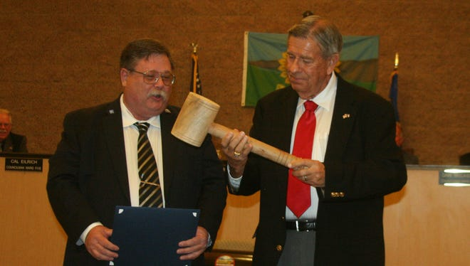 Outgoing Fernley Mayor LeRoy Goodman, right, passes the ceremonial gavel to new Mayor Roy Edgington at the Nov. 19 meeting of the Fernley City Council.
