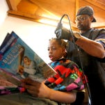 Courtney Holmes, right, listens to Jeremiah Reddick, 9, of Dubuque, as he reads while receiving a free haircut during the Back to School Bash on Saturday, Aug. 8, 2015 in Comiskey Park, in Dubuque, Iowa. Holmes offered his services to children who read while getting their hair cut.