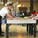 Ben Rhodes, a current driver in the NASCAR XFINITY Series (NXS) plays a game of air hockey with AJ Pittman, 7, of Liberty Twp., while touring 'The Landing', headquarters for The Dragonfly Foundation, on Tuesday afternoon. The Dragonfly Foundation is a non-profit with a mission to provide comfort and joy to kids and young adults enduring cancer and bone marrow transplants.