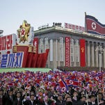 North Koreans wave their national flag as they parade in the capital, Pyongyang, on Saturday to mark 70 years of party rule.