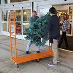 Kim and Candy Varner receive some assistance carrying out their new tree from a store employee Saturday at Kohl's in Chambersburg.