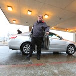 Des Moines City Councilman Chris Coleman disembarks from a ride with the passenger service Uber on Tuesday in Des Moines.