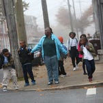 Denise West, 53, walks her two grandsons along with several neighborhood children down the 900 block of N. Pine Street to nearby Stubbs Elementary School, Wednesday, November 12, 2014.