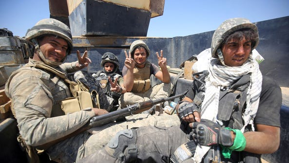 Iraqi government forces gesture as they advance near