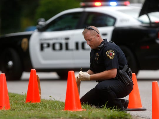 A Springfield police officer recovers shell casings on Fremont Avenue just north of Sunshine Street on Thursday, May 18, 2017. One man suffered non-life threatening injuries in the shooting that involved two cars.