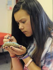 Hailey Boothe, 12, paints a rock at the library.