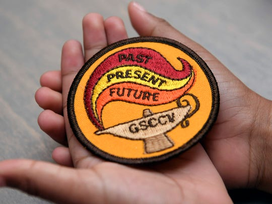 A Girl Scouts holds one of the badges they earned at