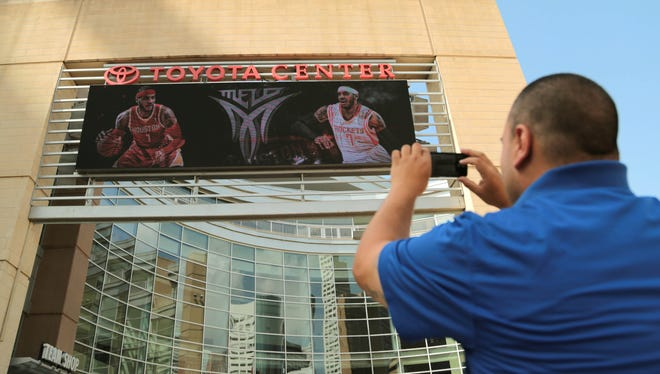 Houston Rockets fan Frank Vasquez takes a photograph of free agent forward Carmelo Anthony wearing Rockets jerseys in composite images on the Toyota Center marquee on Wednesday, in Houston. Anthony was wearing his No. 7 in both renderings, despite the fact that current Rocket Jeremy Lin wears that number. The Rockets would likely have to unload the point guard to snag Anthony.