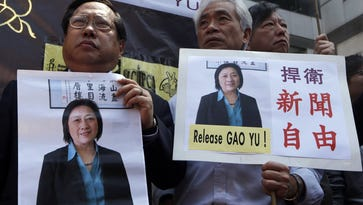 Anti-Beijing protesters hold pictures of jailed veteran Chinese journalist Gao Yu during a rally outside the Chinese central government's liaison office in Hong Kong on April 17.