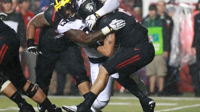 Michigan's Taco Charlton sacks Rutgers quarterback Chris Laviano on Oct. 8 in Piscataway, N.J.