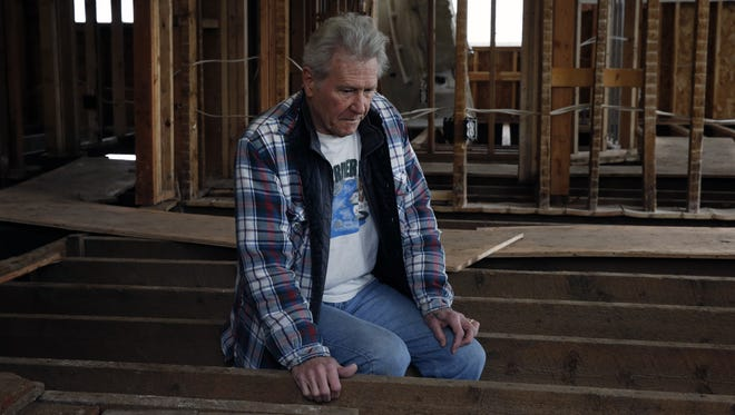 In this March 22, 2014, photo, Charlie Corson sits on the naked beams in the remains of his flood-damaged home in Lyons, Colo. It was destroyed in fall 2013. The retired bus driver and Vietnam vet who has lived in Lyons for more than 20 years has already seen his flood insurance premium jump by a third to nearly $2,000 because he and his wife had to increase their coverage to qualify for a low-interest loan they might need if they decide to rebuild.