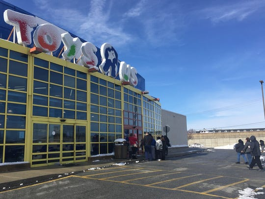 Shoppers walk to front of a Toys 'R Us just before