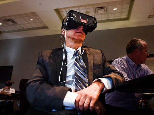 An attendee to the Simulated Workplace presentation held in Maynard Hall at OSU Marion tries his hand at one of the virtual reality training programs on his VR headset.