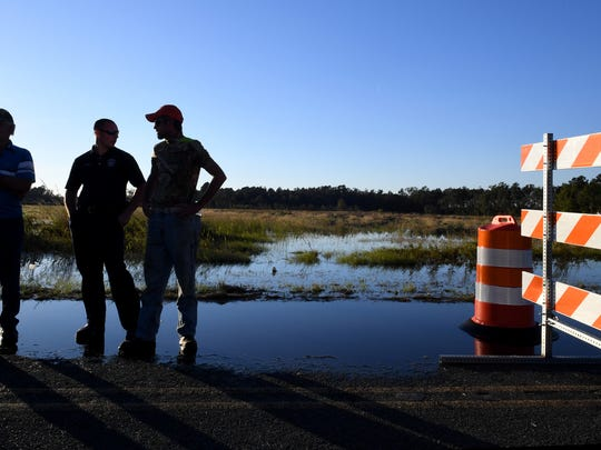 People gather along a flooded Bay Road in Brittons Neck on Thursday. Hurricane Matthew has caused flooding in the Pee Dee region. Thursday, October 13, 2016.