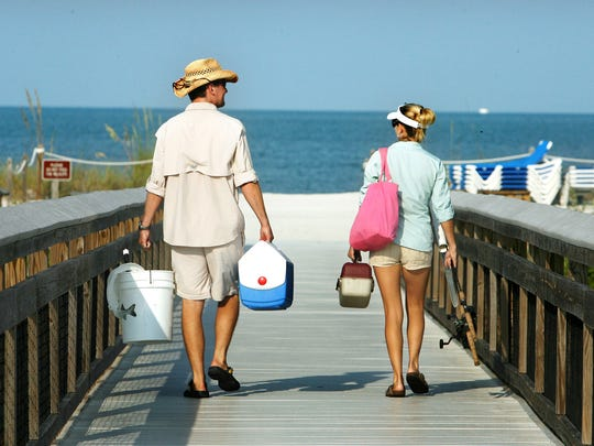 Adam and Kelly Wilkins make their way to the beach at Lover's Key State Park to go fishing on the morning of Thursday, June 11, 2009.