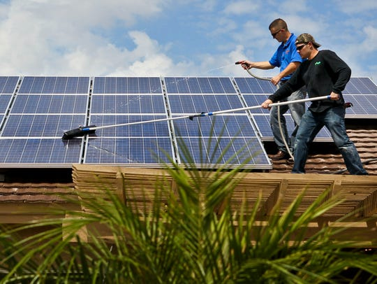 Installers clean solar panels atop a Peoria resident's