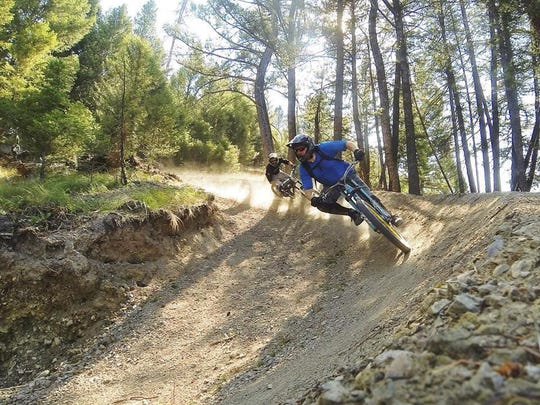 Two mountain bikers ride a berm at the Discovery Bike Park. Discovery Ski Area started offering mountain biking last summer.