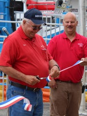 Larry Demorest (left) of Waldo Township cuts the ribbon at the grand opening of the 166th Marion County Fair on Monday. Demorest has been a fair board member for 30 years. Also pictured is Keith Seckel, fair board president.