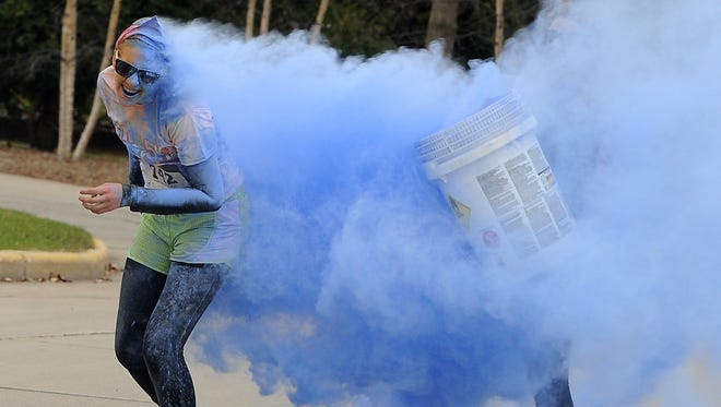 Emma Rieder of Fond du Lac has an entire bucket of blue dumped on her at the blue  burst station during the Agnesian Color Burst 5K held at Lakeside Park in 2014.