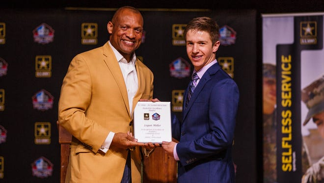 Pro Football Hall-of-Famer Aeneas Williams poses with Award for Excellence finalist Logan Miller at Cabool High School on Monday, March 27, 2017.