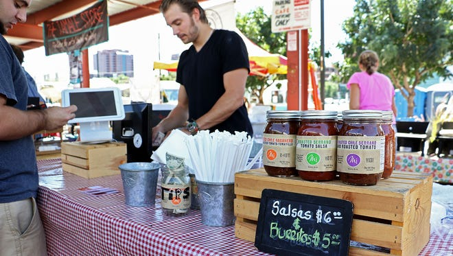 Mi Catering booth - A family owned business that makes burritos and salsas.  They've been at the Market over ten years.  In the picture is pablo and his mom Maria.
