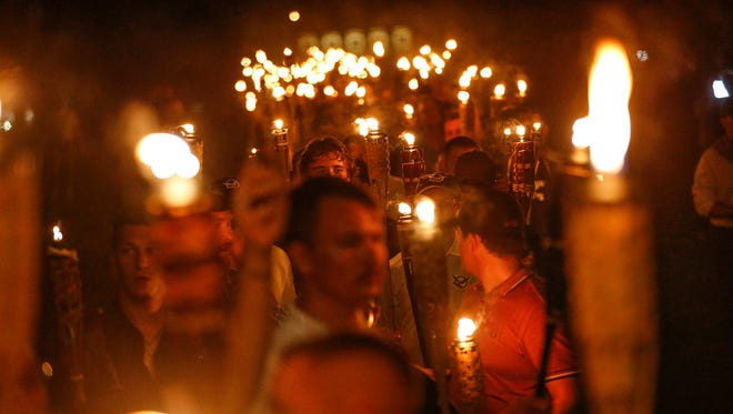 """White nationalist groups march with torches through the University of Virginia campus in Charlottesville, Va., on Friday, Aug. 11, 2017. They were heard to chant, """"You will not replace us"""" as well as """"Jews will not replace us."""""""