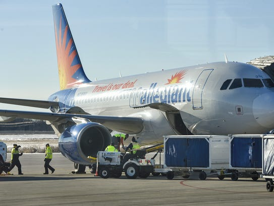 Crews service an Allegiant aircraft Wednesday, Dec.
